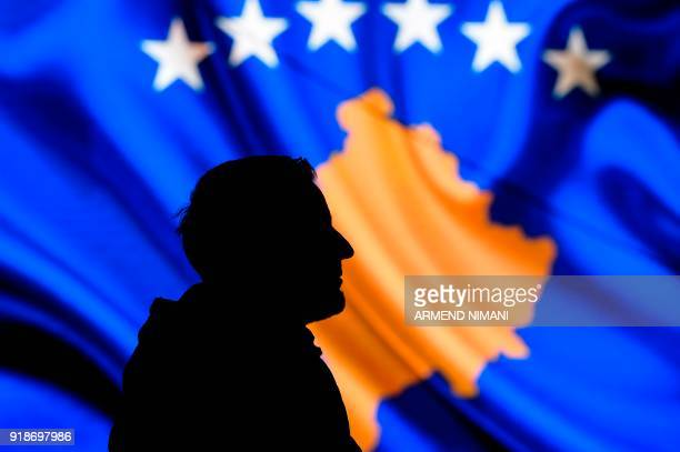 TOPSHOT A man is seen in silhouette as he stands in front of a screen displaying the Kosovo flag during a performance by the United States Air Forces...