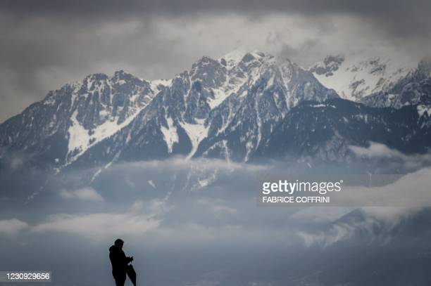 Man is seen in silhouette in a bad weather with snowy Alps mountains in the background on February 2, 2021 in Lausanne.