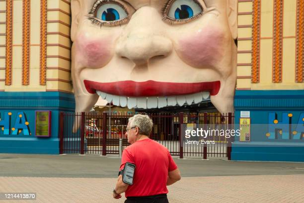A man is seen jogging past a closed Luna Park on March 24 2020 in Sydney Australia Sydney's Luna Park closed its doors to the public on Monday 23...