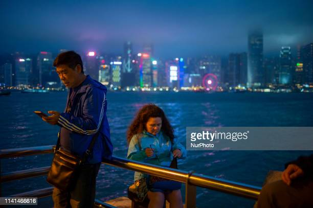 A man is seen looking at his phone while a women is seen packing her glasses into her bag in front of the skyline of Central district in Hong Kong...