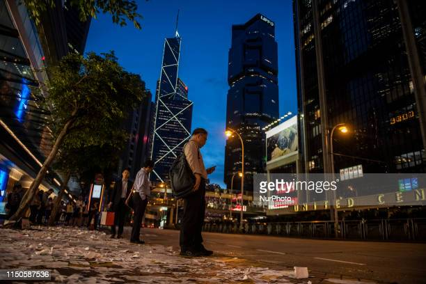 A Man is seen looking at his phone while standing next to paper place on the ground in Hong Kong China 18 June 2019