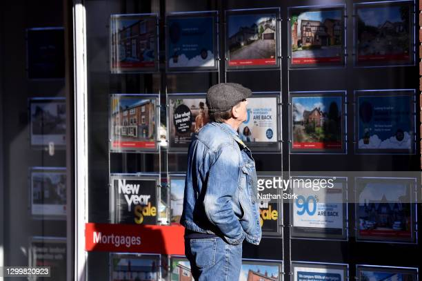 Man is seen looking at houses for sale at an estate agents on February 01, 2021 in Macclesfield , England .