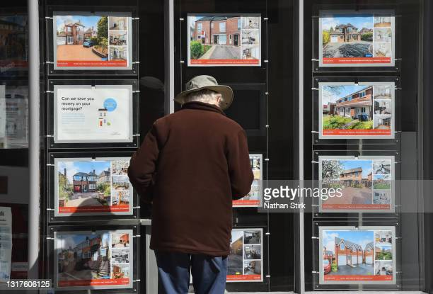 Man is seen looking at houses for sale at an estate agents on May 12, 2021 in Newcastle-Under-Lyme, England .