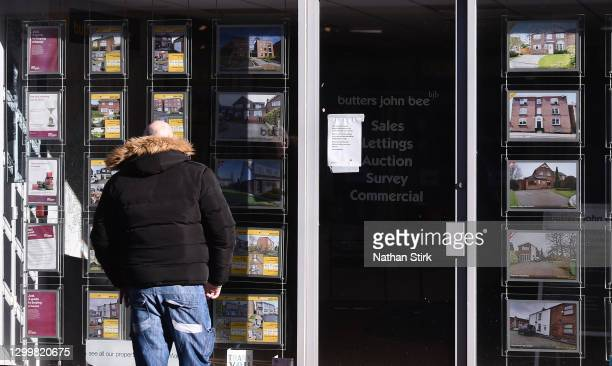 Man is seen looking at houses for sale at Butter Jon Bee's estate agent on February 01, 2021 in Macclesfield , England .