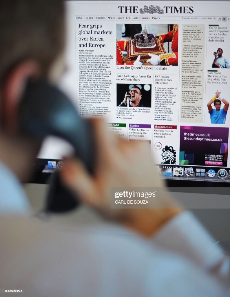 A man is seen looking at The Times newspaper's new website on a computer, in this posed picture, taken in central London on May 25, 2010. News International has launched new websites for its British daily and Sunday Times newspaper titles, offering a free trial period for customers. After the trial period customers will be asked to pay £1.00 a day or £2.00 for a week to access the sites. The Times' readership is currently 1.8 million and the Sunday Times has a readership of 3.2 million.
