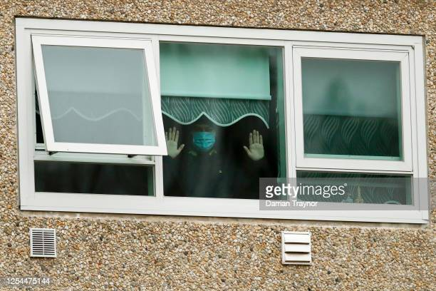 Man is seen looking out a window of the Flemington Towers Government Housing complex on July 06, 2020 in Melbourne, Australia. Nine public housing...