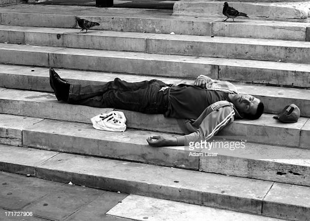 Man is seen lying down on inner city steps, seemingly asleep. Pigeons walk about near him.