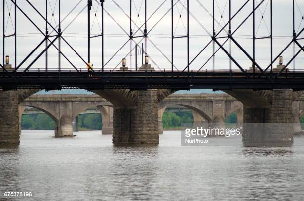 A man is seen mounting a onemile marker on Walnut St Bridge over the Susquehanna River in Harrisburg PA on the morning of April 30 2017 Diminishing...