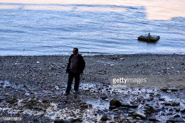 A man is seen on the beach during low tide as he scans the ground with a metal detector London on September 13 2018