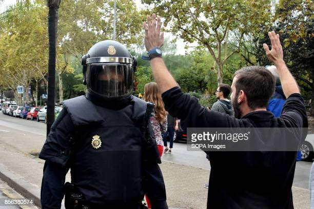 A man is seen raising his arms front of a spanish policeman National Police entered by force in the High School of L´Hospitalet City where they have...