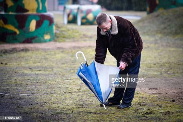 A man is seen repairing an umbrella in Bydgoszcz Poland on March 9 2019