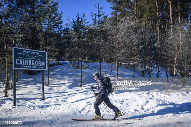 Man is seen skiing past a sign reading 'Welcome to Cairngorm' on February 11, 2021 in Aviemore, United Kingdom. The village of Carrbridge in Badenoch...