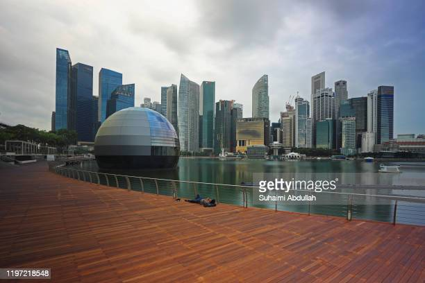 Man is seen sleeping by a floating glass orb, allegedly to be the new Apple flagship store at Marina Bay Sands, with the Central Business District in...