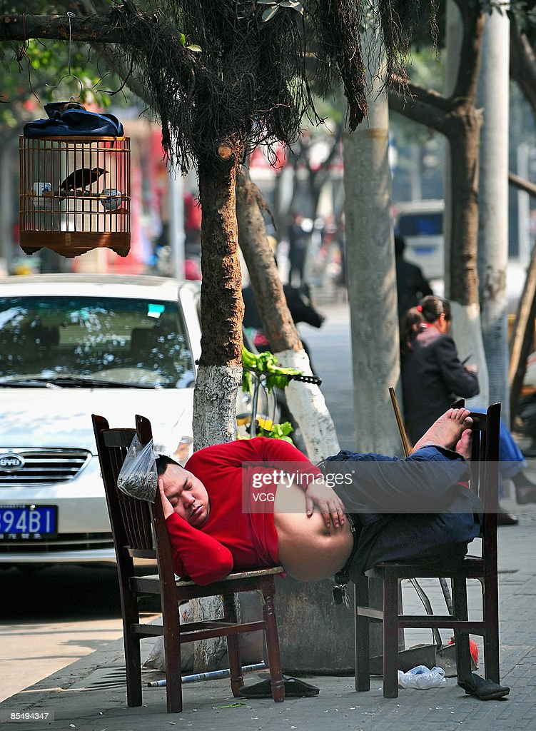 A man is seen sleeping on chairs along the roadside on March 18, 2009 in Chengdu, Sichuan Province of China. The uprising temperature marks the coming of spring.