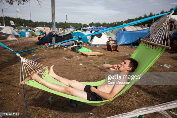 A man is seen smoking a cigarette on a hammock at the 2017 Woodstock Festival Poland on August 4 2017 in Kostrzyn Poland The threeday rock music...