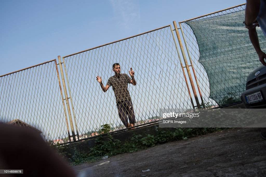 A man is seen standing next to a wire fence. Refugees trying ...