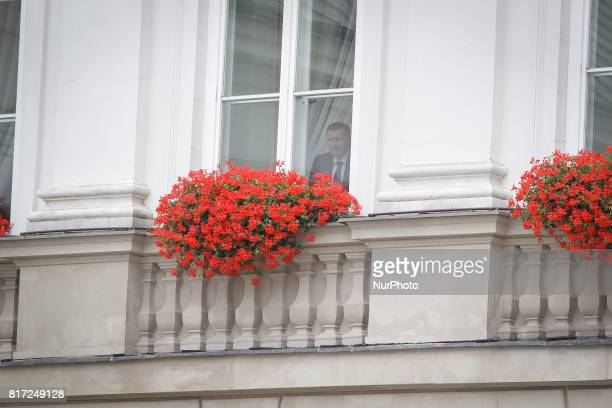 A man is seen staring out of a window of the presidential palace in Waraw ahead of the visit of the Duke and Duchess of Cambridge in Warsaw on 17...