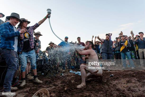 A man is seen stripped naked and taking a hit from a gas powered beer pipe at the 2017 Deni Ute Muster on September 30 2017 in Deniliquin Australia...