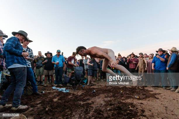A man is seen stripped naked before throwing himself into a makeshift mud pit on the wild final evening of the 2017 Deni Ute Muster on September 30...