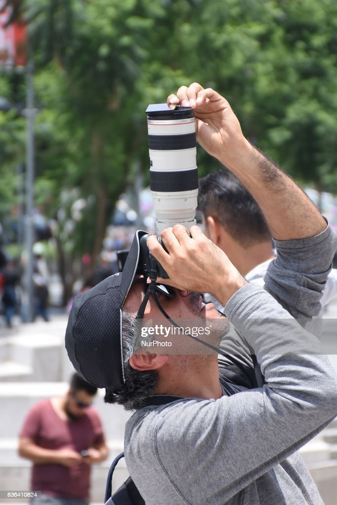 A man is seen take a photo of the Partial Solar Eclipse viewed from the Mexico City on August 21, 2017 in Mexico City, Mexico