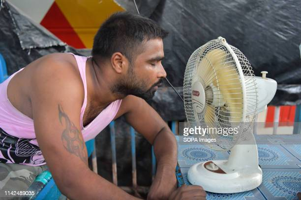 Man is seen taking a break from work cooling himself down by a fan. With maximum temperature near 39°C, high humidity and heat wave from central...
