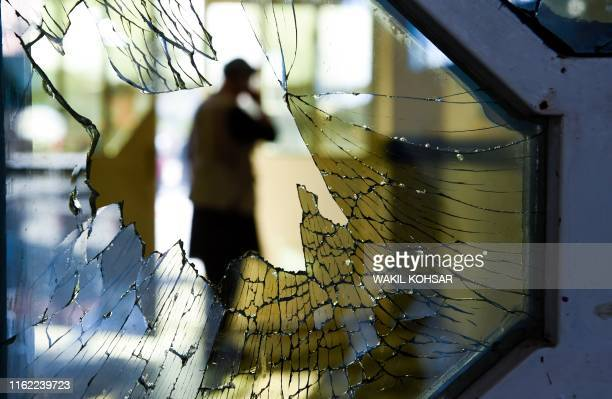 TOPSHOT A man is seen through a broken window of a wedding hall after a deadly bomb blast in Kabul on August 18 2019 More than 60 people were killed...