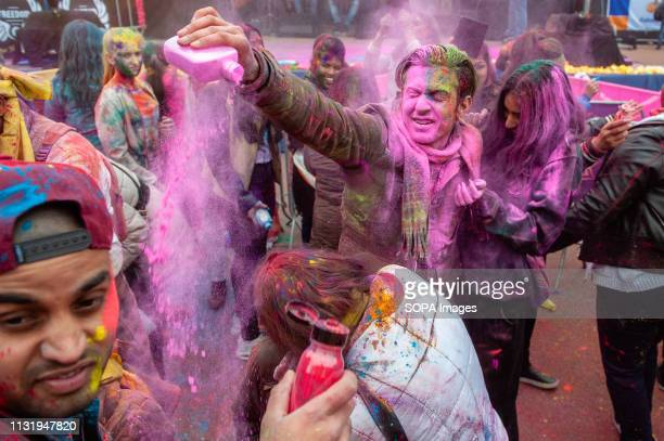 A man is seen throwing colored powders to a woman Millions of people around the world celebrate the annual Holi Hangámá Festival also known as the...