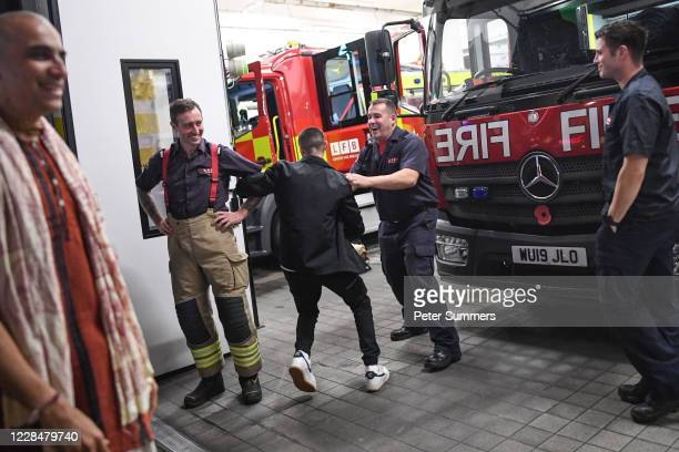 Man is seen trying to dance with Firefighters on September 12, 2020 in London, England. From Monday, September 14, groups of more than six will be...