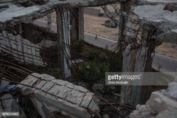 A man is seen walking in the street from inside a destroyed apartment block in the Beit Lahia neighborhood on July 24 2017 in Gaza City Gaza For the...