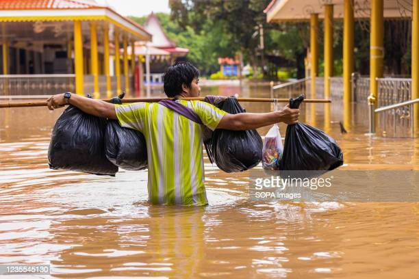 Man is seen walking on a submerged road. Lopburi and many provinces in Thailand were hit by flash flood due to the heavy rainfall.