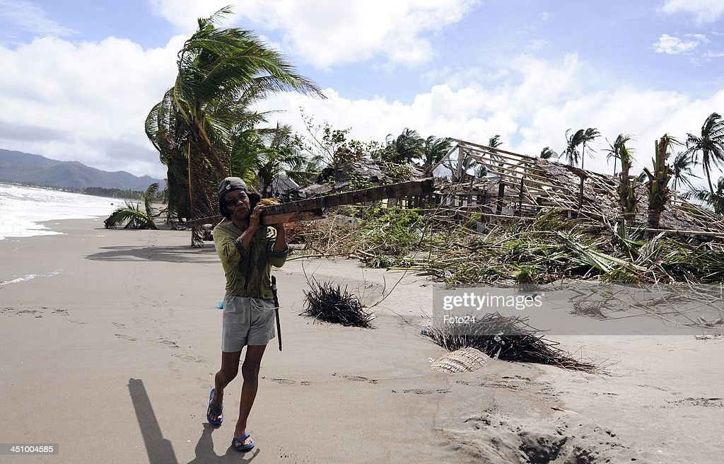A man is seen walking on the beach carrying salvaged wood on November 20, 2013, in Abuyog, Philippines. Typhoon Hyaina hit the Philippines on November 8, 2013, and was recorded as the second deadliest typhoon in that region.