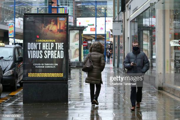 Man is seen wearing a face masks walking through the streets of Manchester on January 28, 2021 in Manchester, England.
