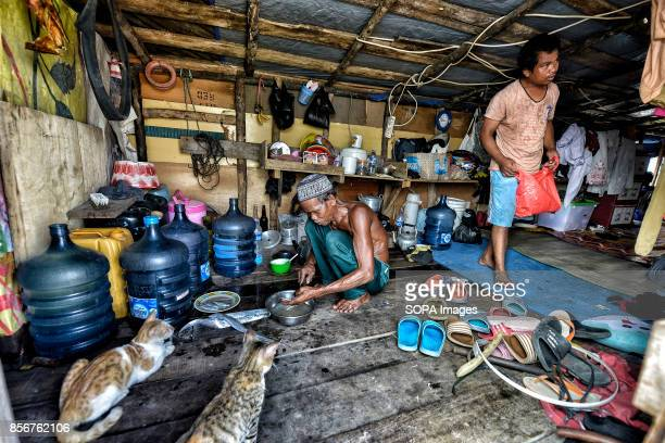 A man is seen while cleaning a fish to eat at his house in the Pasar Ikan neighborhood of Jakarta In April last year hundreds of soldiers and police...