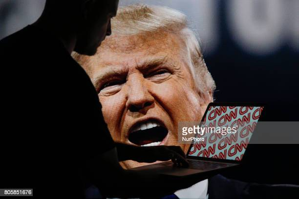 A man is seen with a laptop depicting the CNN news network logo with Donald Trump appearing on a TV screen in the background in this photo...