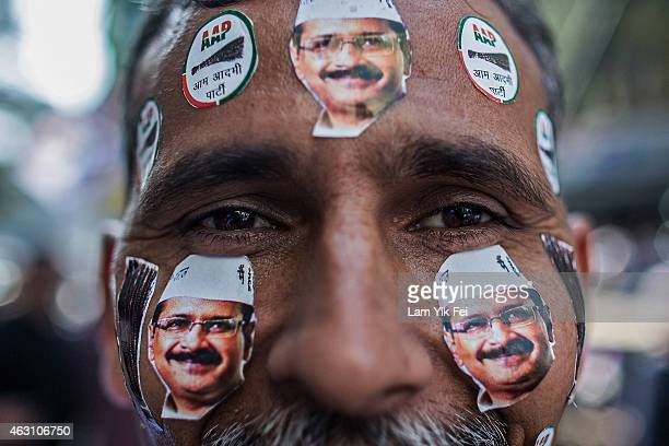 A man is seen with Aam Aadmi Party leader Arvind Kejriwal stickers on his face as he watches the results of Delhi Assembly Elections at the party...