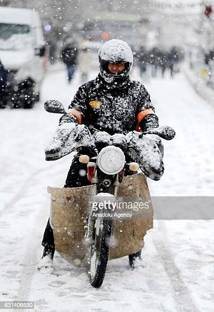 Man is seen with his motorcycle on the snow covered road as snow falls in Usak, Turkey on January 10, 2017.
