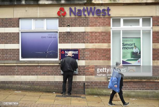 Man is seen withdrawing cash from NatWest Bank on October 30, 2020 in Newcastle-under-Lyme, England. HSBC Chief Executive Noel Quinn said the bank...