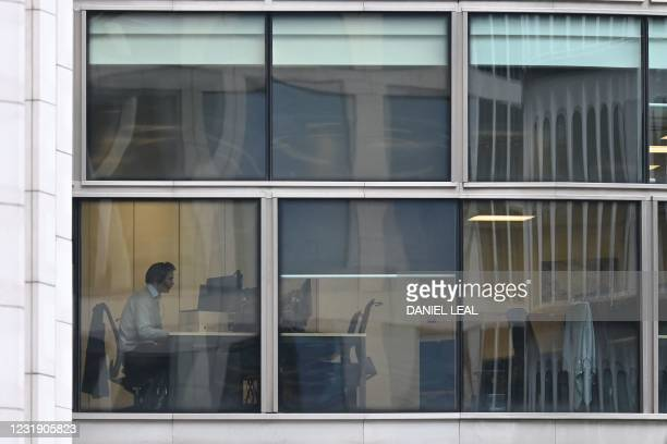 Man is seen working at a desk in an office in the City of London on March 24, 2021 as life continues with England following a government roadmap to...