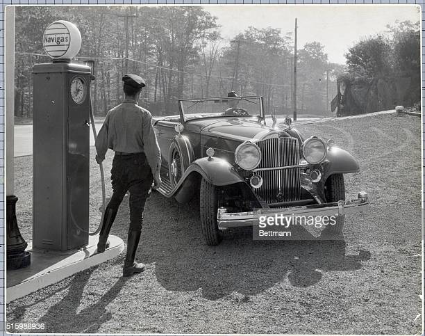 A man is shown pulling his car into a Navigas gas station as the attendant prepares to fill the automobile Photograph circa early 1930's