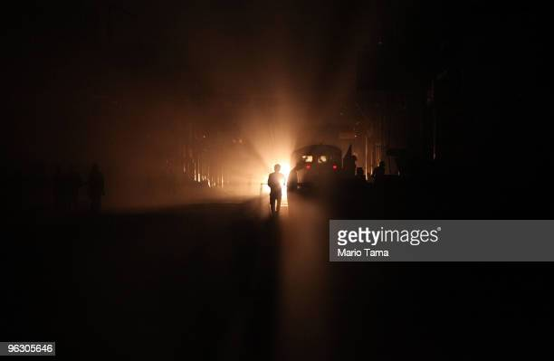 A man is silhouetted by car headlights in the otherwise darkened street as electricity remains out January 31 2010 in PortauPrince Haiti The UN began...