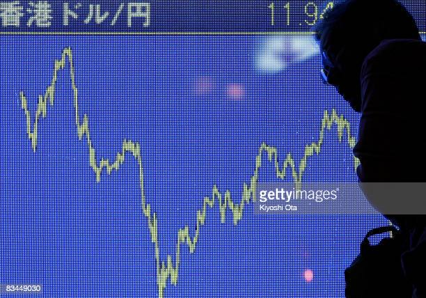 A man is silhouetted on an electronic board showing the 12month movement of the Hong Kong dollar rate against the Japanese yen on October 27 2008 in...