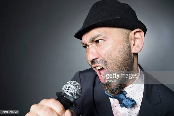 Man is singing a song hard wearing a suit