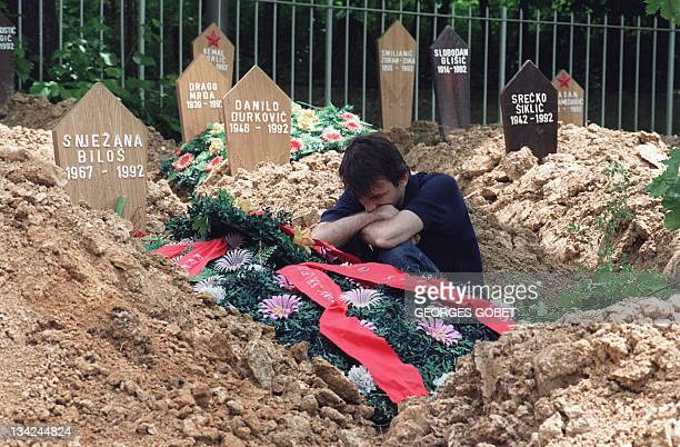 A man is sitting among new ground graves in the Sarajevo Hero's Partisan cemetery near the hospital on June 7 1992 This Serbian cemetery which was...