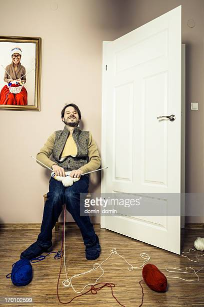 Mann sitzt auf einem Stuhl und Stricken winter Mütze, humorvolle