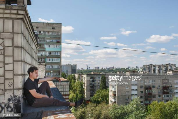 man is sitting on the edge of the roof in the big city - kiev stock pictures, royalty-free photos & images