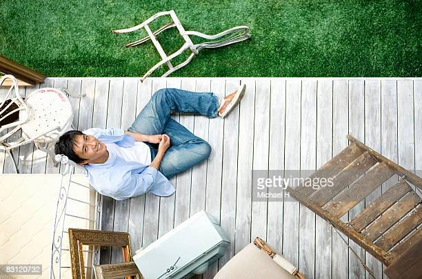 Man is sitting on wood floor in  garden