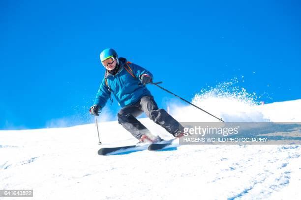 Man is skiing in the Alps with blue sky