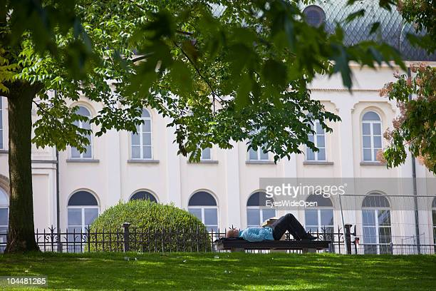 Man is sleeping on a bench in the Leopold Park a recreational area near the building of the European Union EU on September 10 2010 in Brussels Belgium
