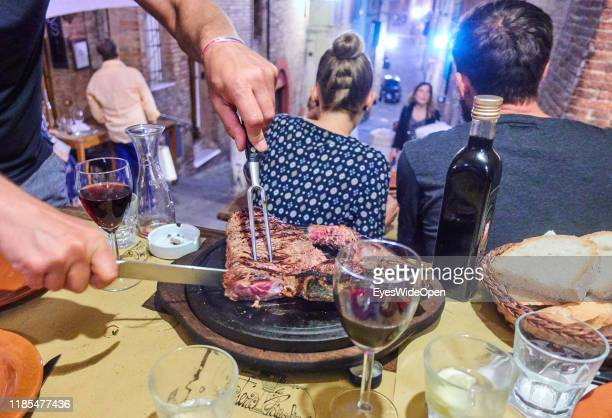 A man is slicing a Bistecca alla Fiorentina a big steak and read wine on June 16 2019 in Siena Italy