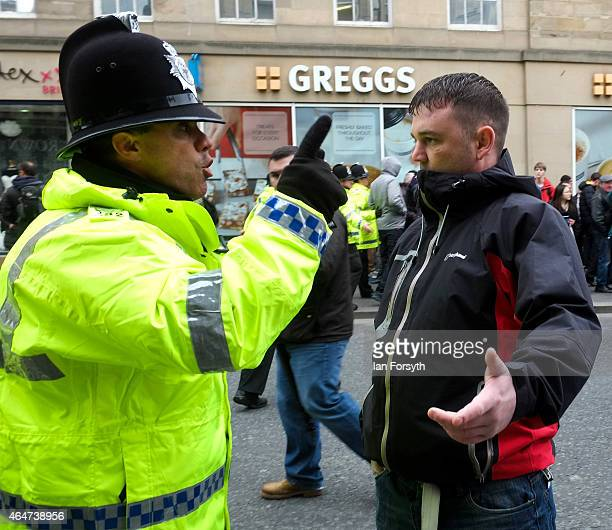 A man is spoken to by a police officer as members of right wing movement Pegida take part in a demonstration on February 28 2015 in Newcastle upon...